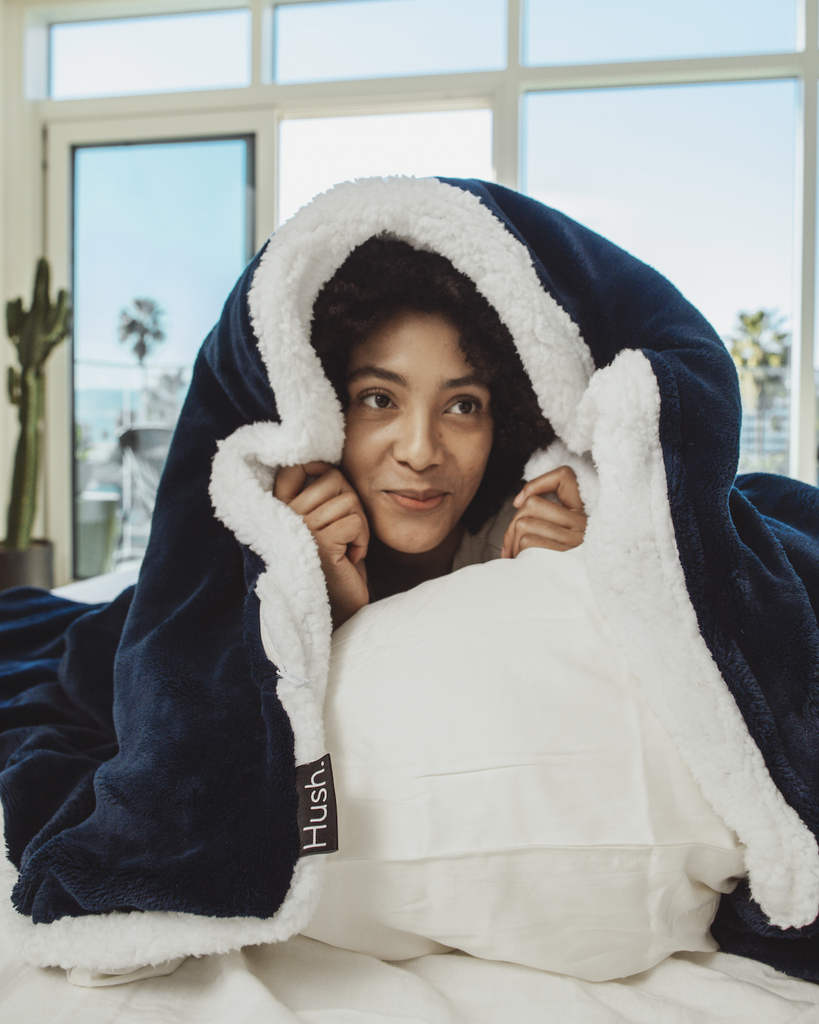 Smiling woman covering herself with a blanket while in bed