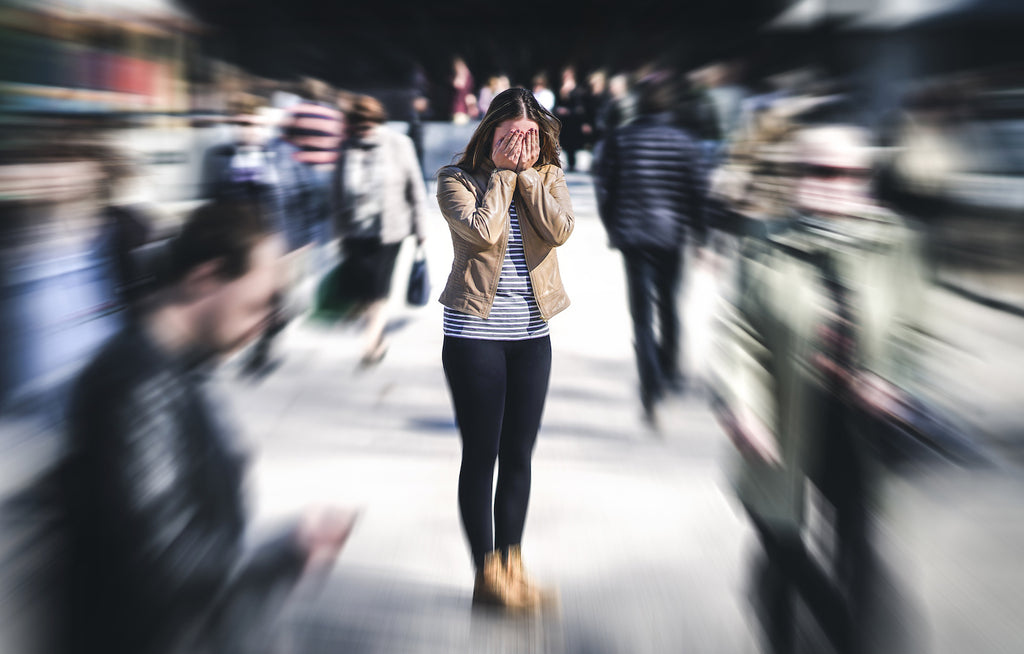 sensory overload anxiety: woman in a crowd covering her face