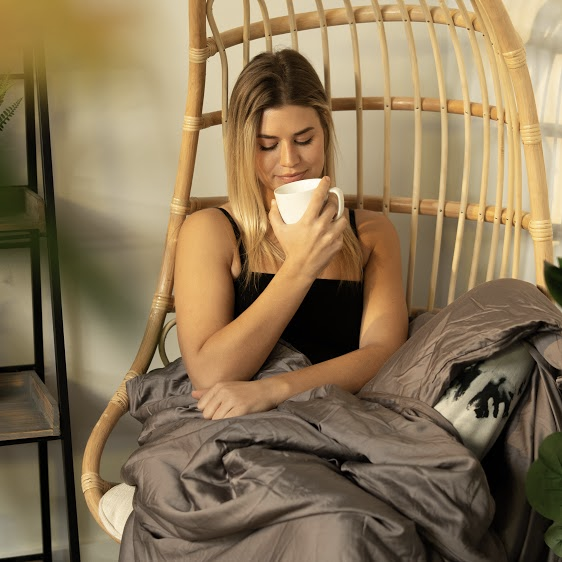 Woman holding a coffee mug with a blanket while sitting on a bamboo swing chair