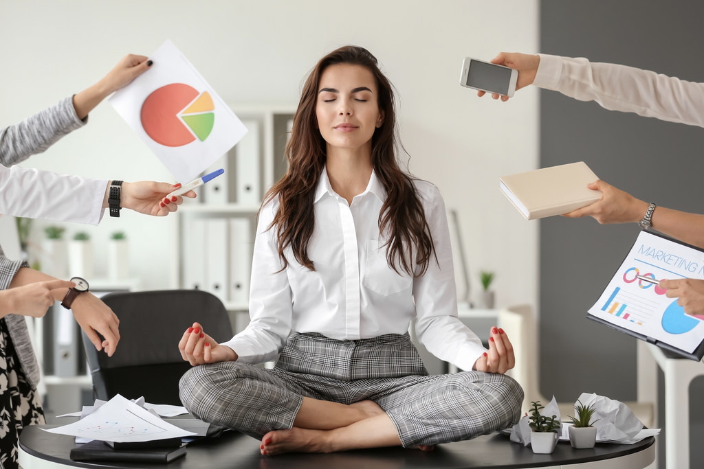 how to relax after work: Woman meditating on a table while being pressured by her colleagues
