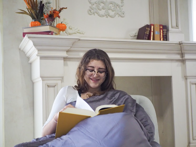 Smiling woman sitting on a chair with a blanket while reading a book