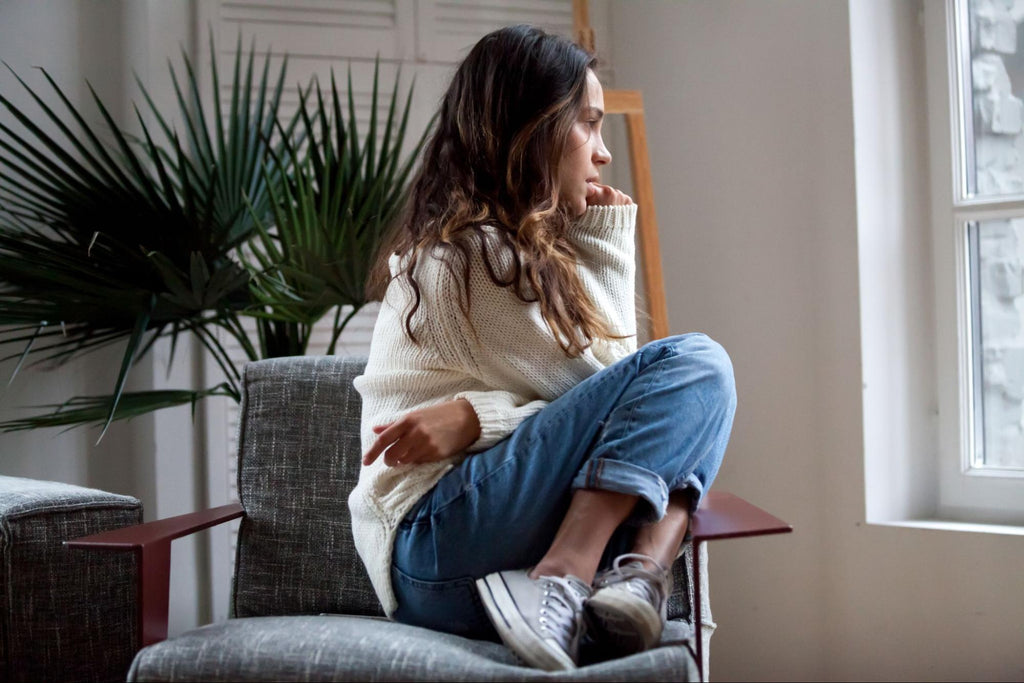 how to manage anxiety without medication: Anxious woman curled up in a chair while staring out the window