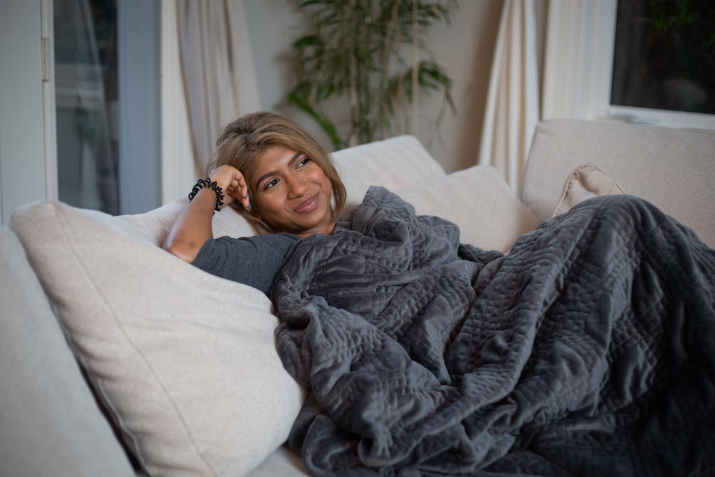 Smiling woman sitting on the couch with a weighted blanket