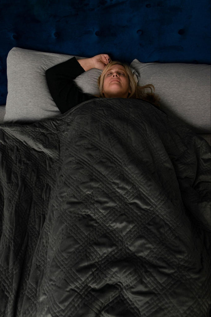 Woman sleeping in bed with a weighted blanket