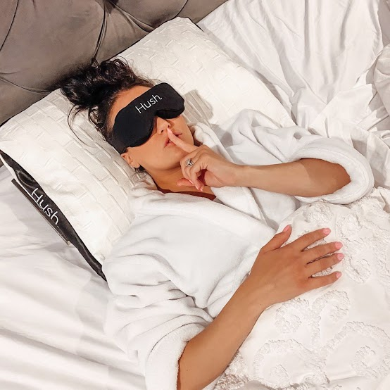 too hot to sleep: Woman with an eye mask lying in bed while her finger is on her lips