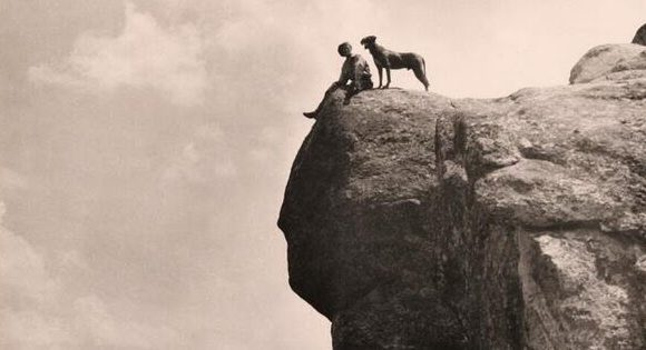 man and dog on rock ledge vintage wolf and iron