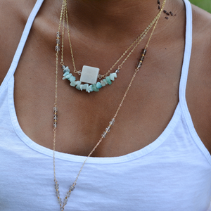 Close-up of a Young African American Woman in a White Tank Top wearing the Delicate Smokey Quartz Positano in 14k Gold-Fill