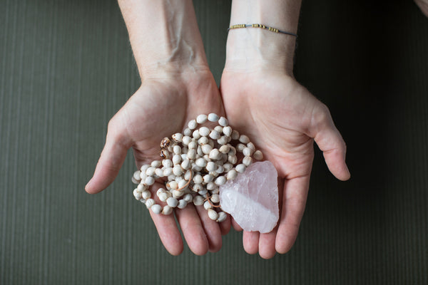 hands holding mala beads and rose quartz crystal