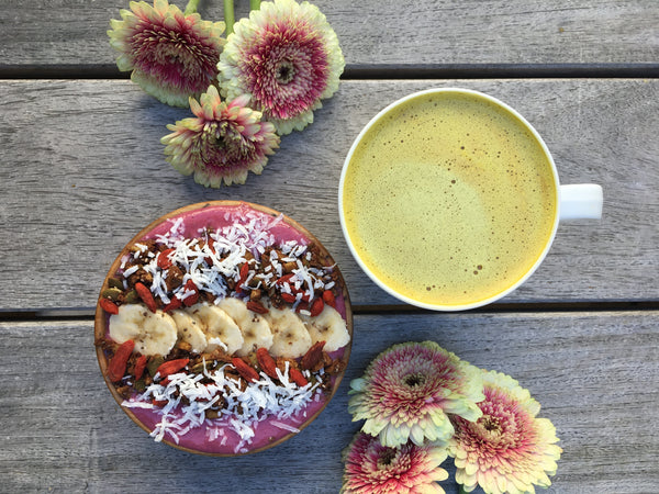 smoothie bowl with daisies and a golden latte, on wood background