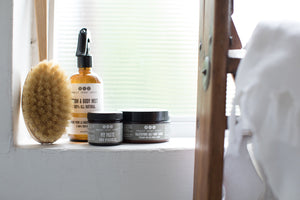 scrub brush with room & body mist, pit paste and salt scrub by Really Great Goods, on windowsill with ladder and towel