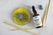 Lem Love Room & Body Mist with lemongrass, crystal and yellow plate with air plant, aerial view.