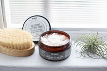 salt scrub by Really Great Goods on windowsill with air plant and body brush