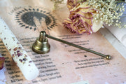 Brass candle snuffer next to a floral infused candle.