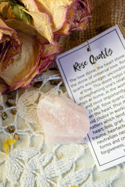 Rough rose quartz stone on a lace tablecloth with informational card