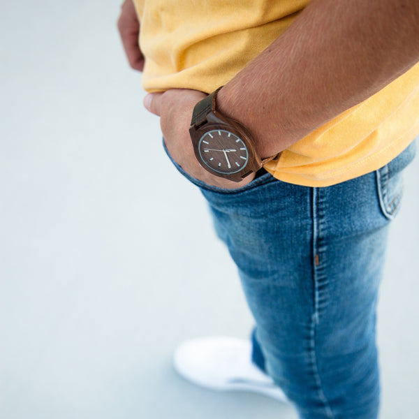man wearing jeans with yellow shirt and wooden watch on wrist