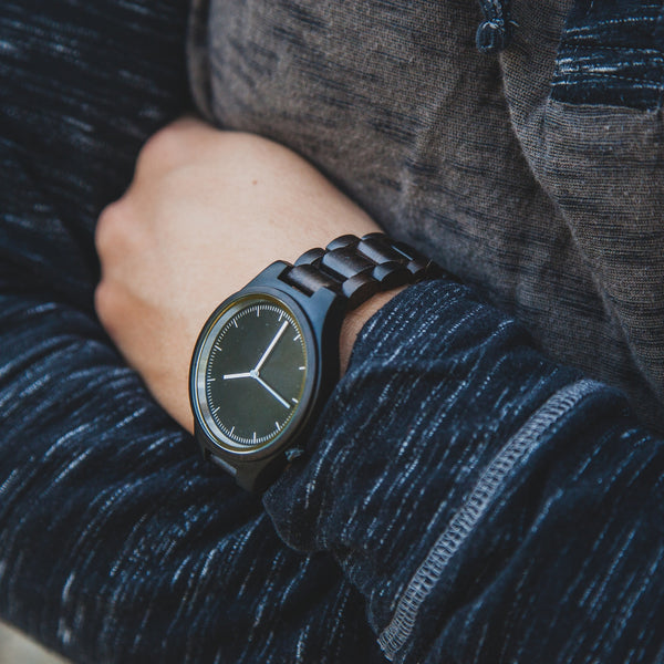 wooden watch on mans wrist arms crossed