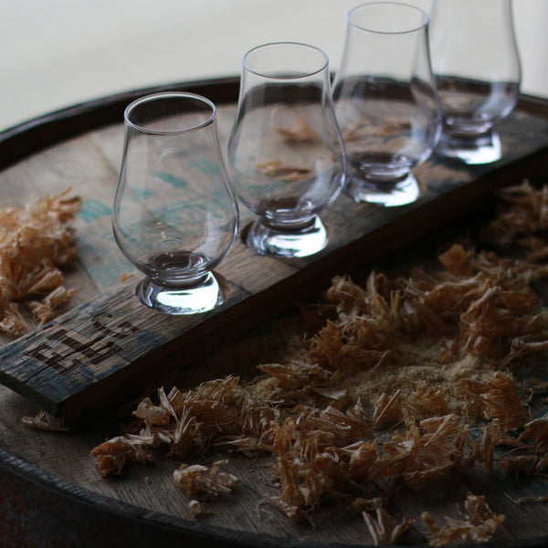engraved whiskey flight board with whiskey glasses on barrel