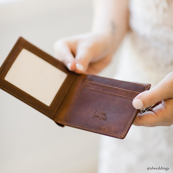 engraved leather wallet held by a bride