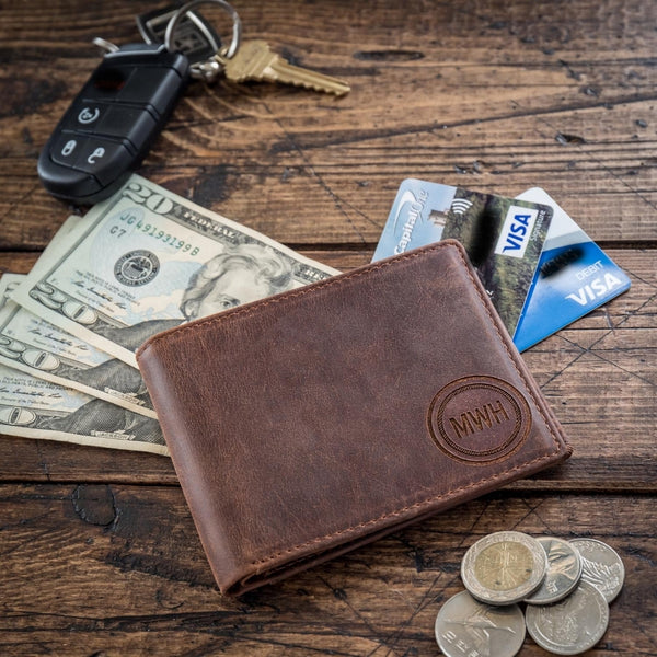 monogramed leather wallet on table with cash credit cards and coins
