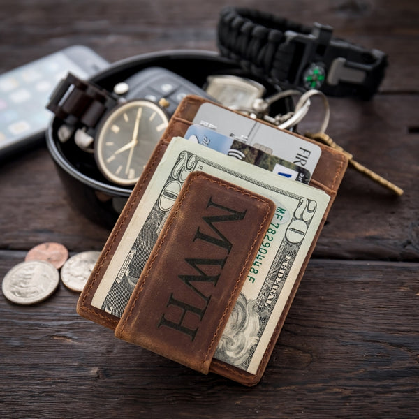 leather money clip on table with watch and change