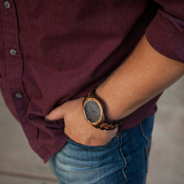 wooden watch on a wrist with a maroon shirt