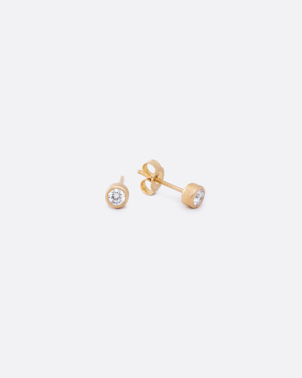 aa74551af a pair of diamond stud earrings with yellow gold bezel settings. the one on  the