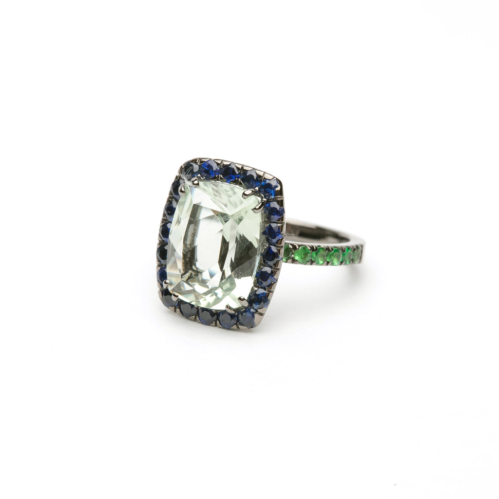 the Cocktail ring features a cushion cut prasiolite center stone surrounded by round blue sapphires set in 18 karat black rhodium gold. Pave round tsavorite garnets accent shank.