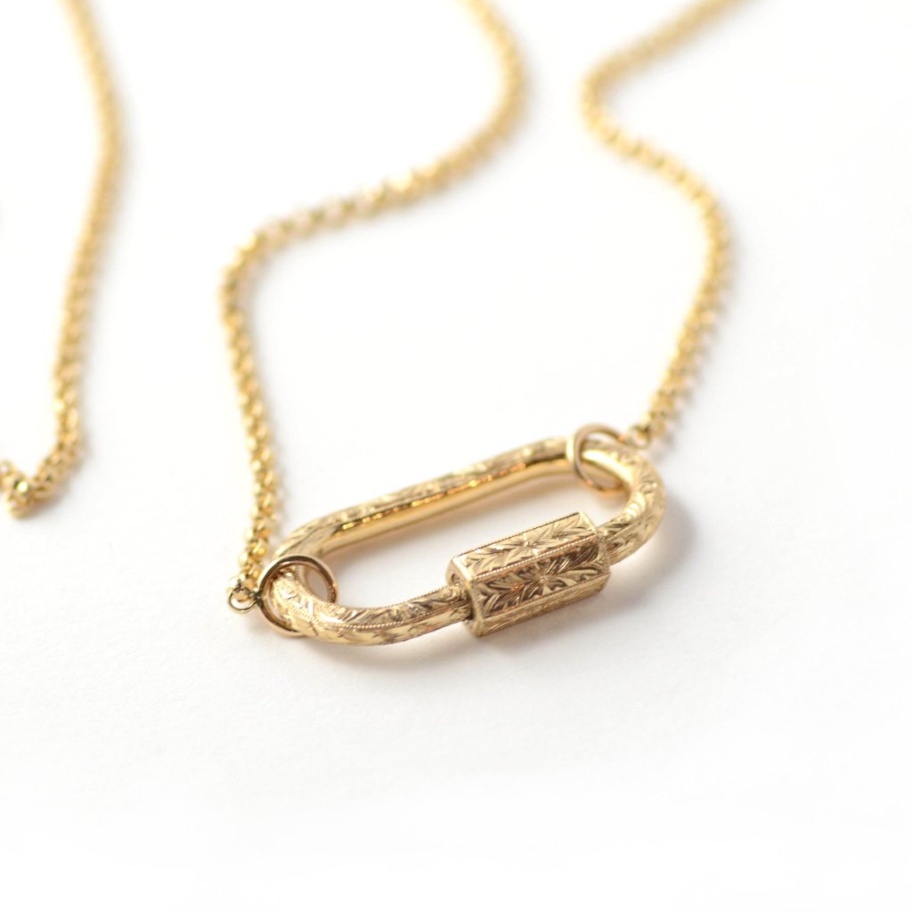 Marla Aaron Hand engraved lock shown in yellow gold on rolo chain