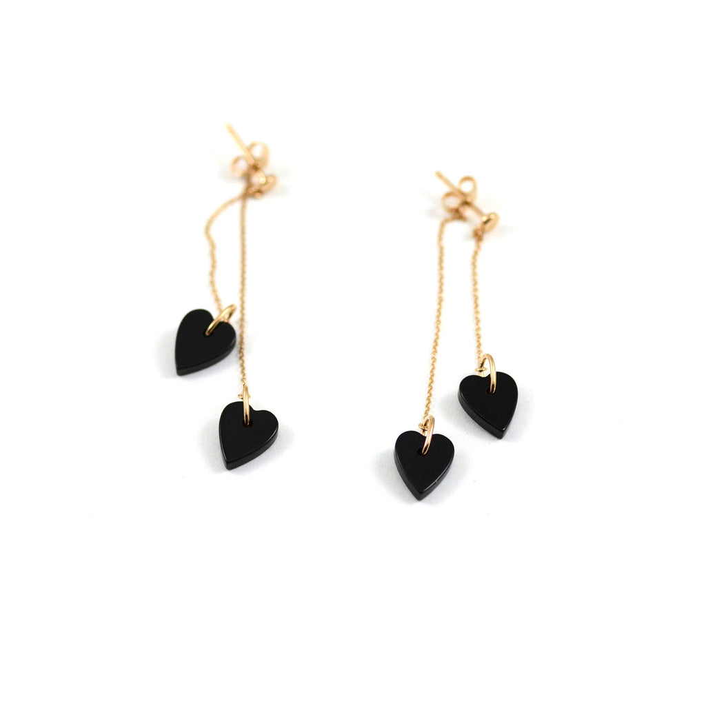 Ginette NY earrings. From the Angele collection. Two black onyx hearts are suspended from 18kt rose gold chains. A contemporary look with a bit of an edge. Heart size is approximately 10 mm, chain lengths are approximately 29 and 45 mm.