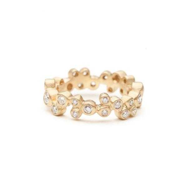 Annie Fensterstock Vega Ring is an infinity band of yellow gold featuring white bezel set diamonds