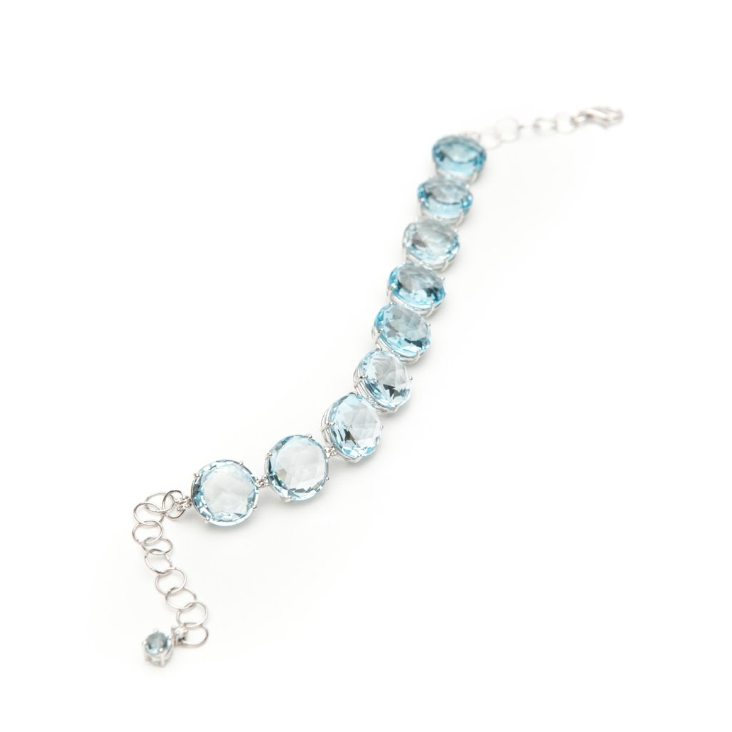Made by hand, this bracelet features double rose cut blue topaz bracelet are accented with round white diamonds all set in 18 karat white gold.