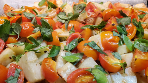 Roasted potatoes and tomatoes with fresh chopped basil on top.