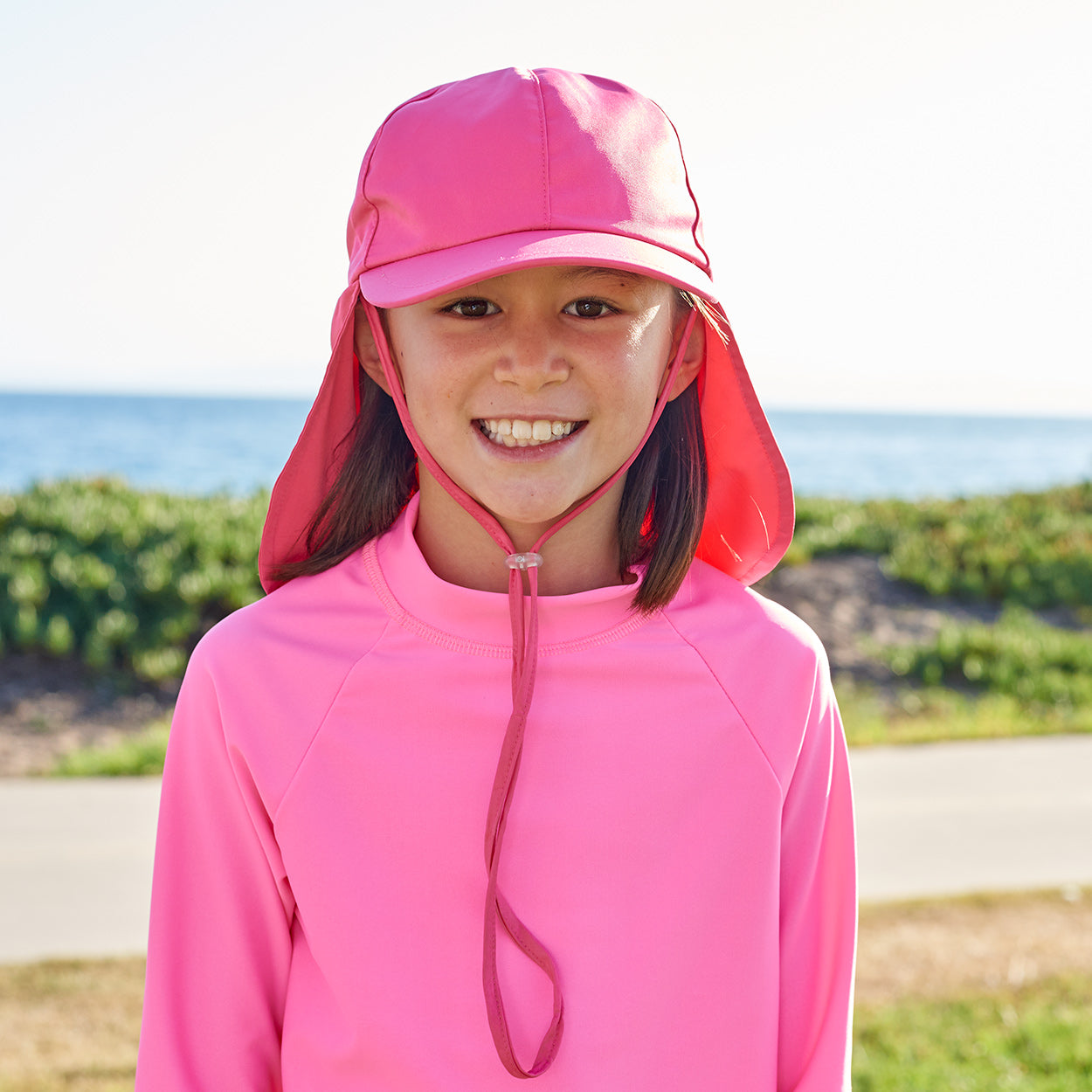 Girls Pink Legionnaire Sun Hat Upf 50 Size S Xl Girl Smiling Wearing Pink Hat on the Side Walk Sunpoplife