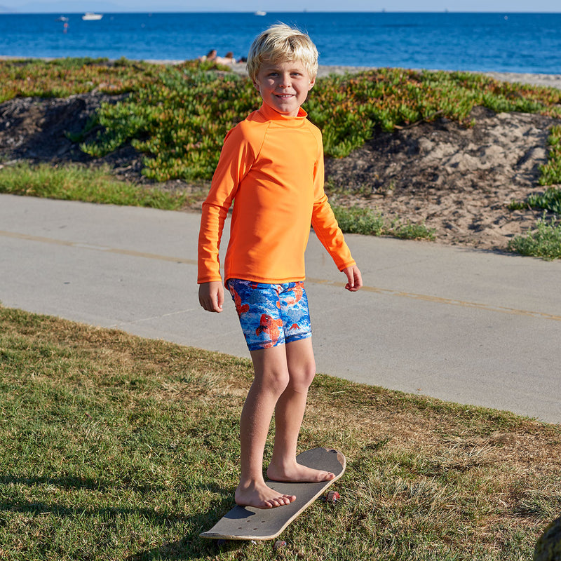 Bright Orange Kids Long Sleeve Rash Guard Top Upf50 Boys Girls Unisex Size 2 12 Boy Wearing a Bright Orange Top Standing on a Skateboard Sunpoplife