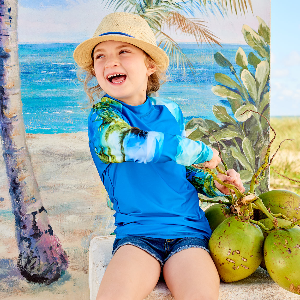 Hawaiian Long Sleeve Rash Guard Top Upf50 Kids Boys Girls Size 2 12 Unisex Green Blue Palm Trees Geo Tropical Girl Wearing A Hat Sitting Against A Beach Scene Holding Coconuts Sunpoplife