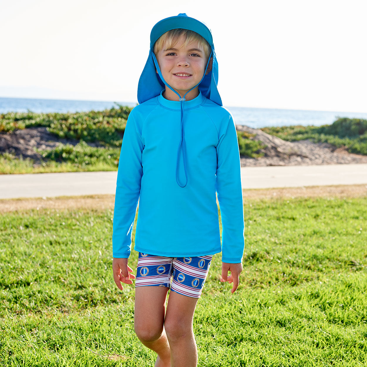 Island Blue Kids Long Sleeve Rash Guard Top Upf50 Boys Girls Unisex Size 2 12 Boy Walking on a Grassy Patch by the Beach Sunpoplife