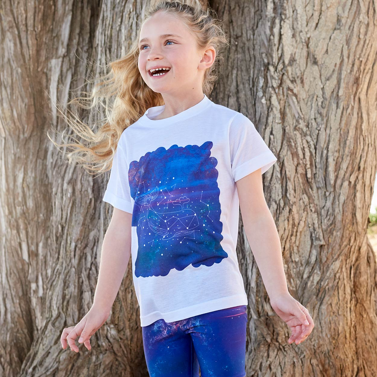 Kids Whale Graphic Tshirt Size Xs L White Purple Unisex Cosmos Cetus Constellations Surfer Girl Smiling In Front Of A Brown Tree Sunpoplife