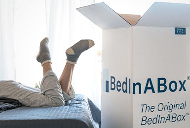 bed in a box next to person on bed