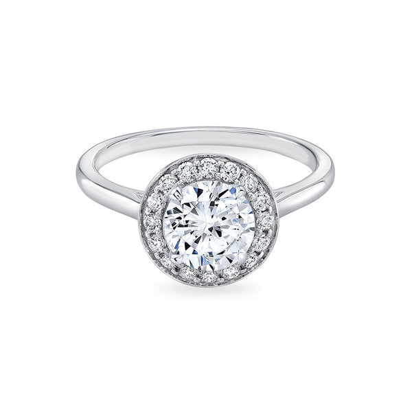 The perfect embodiment of a classic halo silhouette, the Blossom Pave Halo Engagement Ring features a central diamond framed by a radiant circle of Pave set diamonds. Four subtle, petal shaped prongs hold the central stone, while a softly squared band adds a structural but feminine element to this cathedral setting. This ring will sit flush with a wedding band.