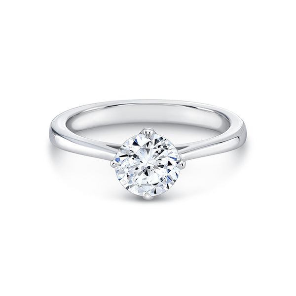 Four petal-shaped prongs mark the compass points that hold the center diamond. A half dome shaped band elegantly tapers to fine cathedral shoulders on this solitaire ring. Nests comfortably with an eventual accompanying wedding band.