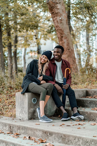 Man and woman sitting on a concrete slab wearing Vessi Cityscapes in autumn