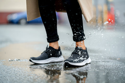 Woman in black Vessi waterproof shoes walking on a wet path