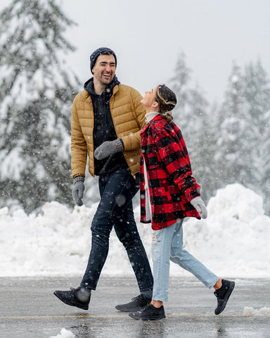 A man and a woman walking through a snowy city wearing waterproof shoes.