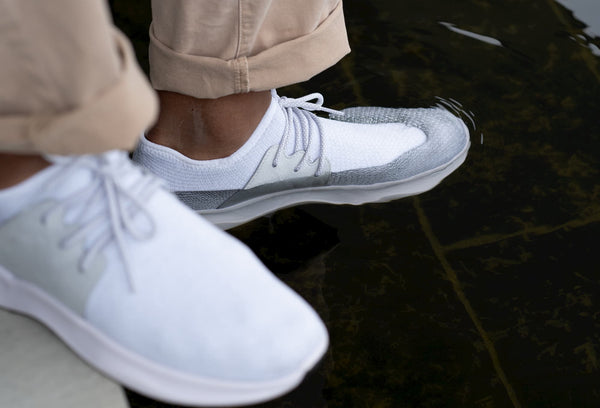 Man wearing Vessi rain shoes immersing his foot in the water