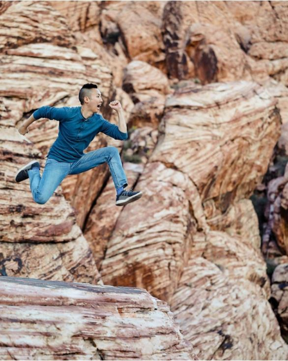 A happy man jumping across giant red rocks while wearing his Vessi Charcoal Grey Cityscapes