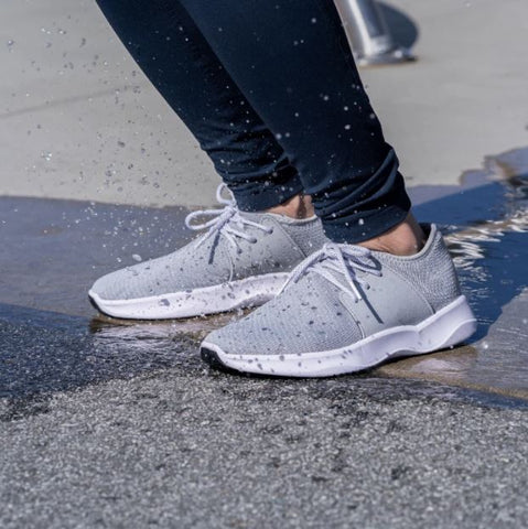 A close up shot of a woman's Vessi waterproof walking shoes splashing in puddles on pavement