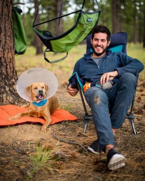 A man wearing Vessi Storm Black Cityscapes while sitting in a camp chair next to his dog out in the wilderness