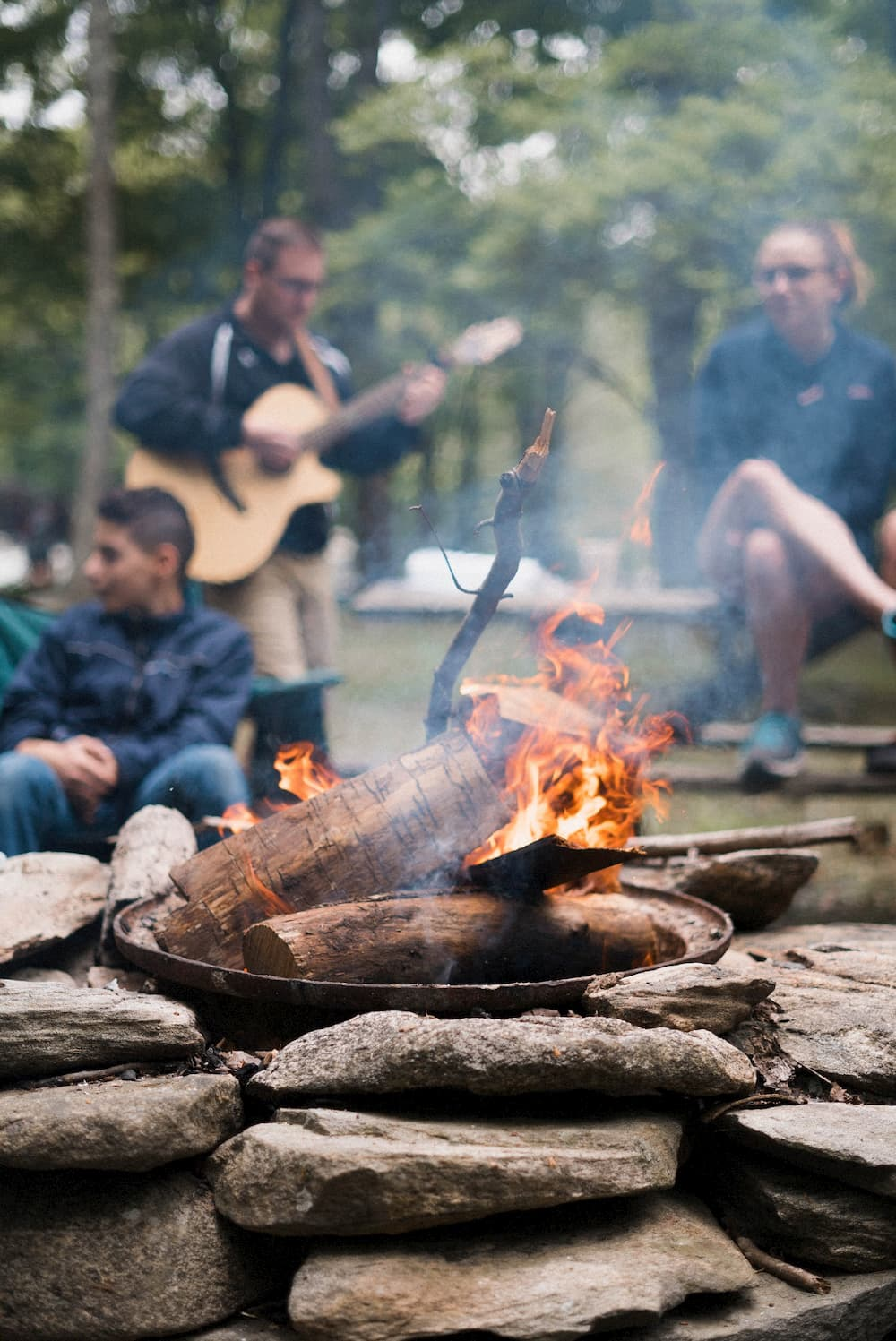 A group of friends gathered around a campfire, playing guitar and chatting