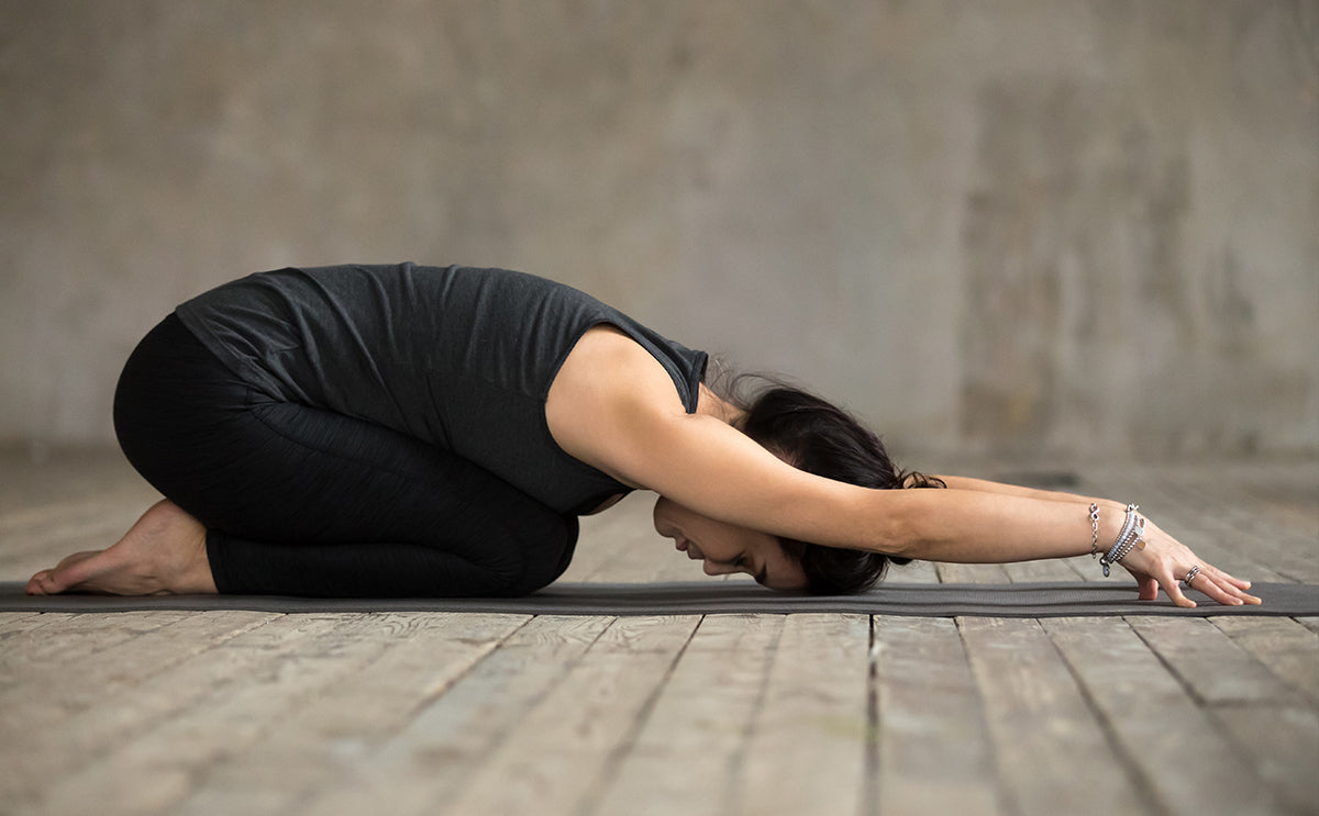 woman doing child's pose on yoga mat