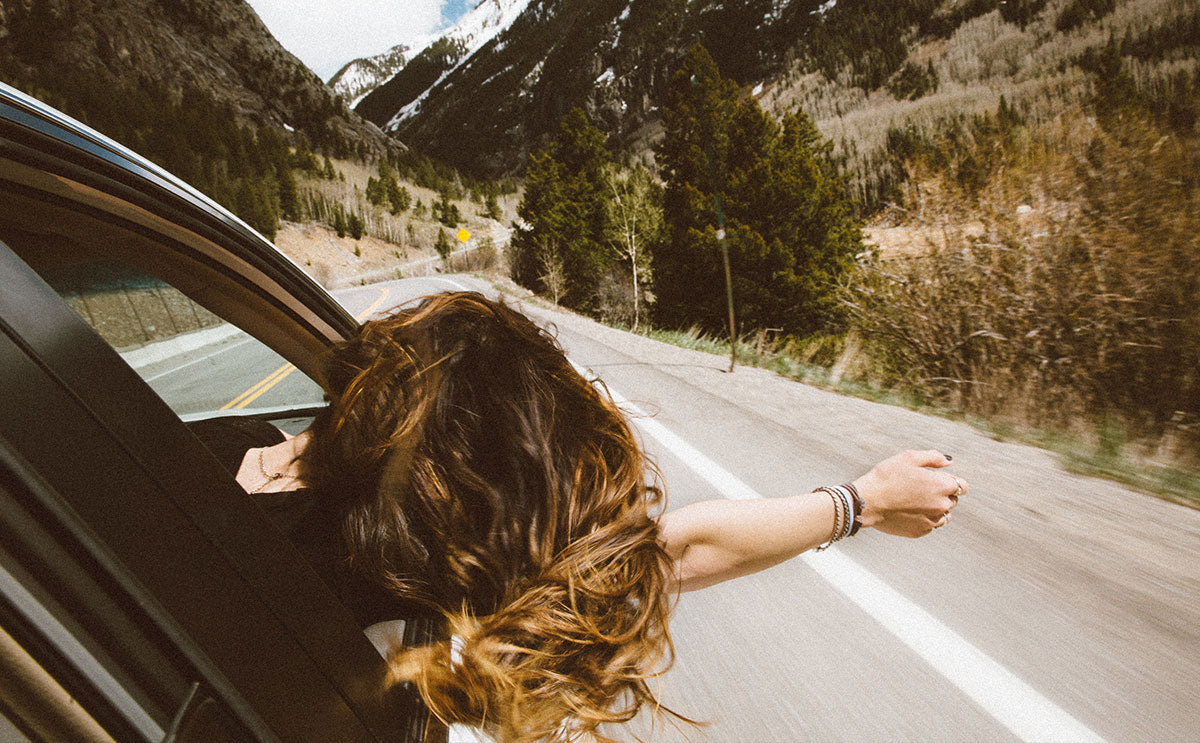 woman leaning out of window on road trip